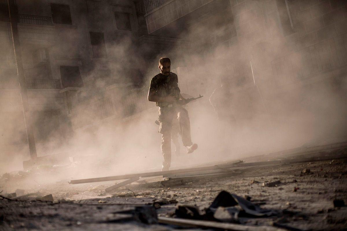 Un combatiente rebelde sirio corre tras atacar un vehículo armado del ejército sirio en el distrito de Izaa, Alepo, 2012. MANU BRAVO