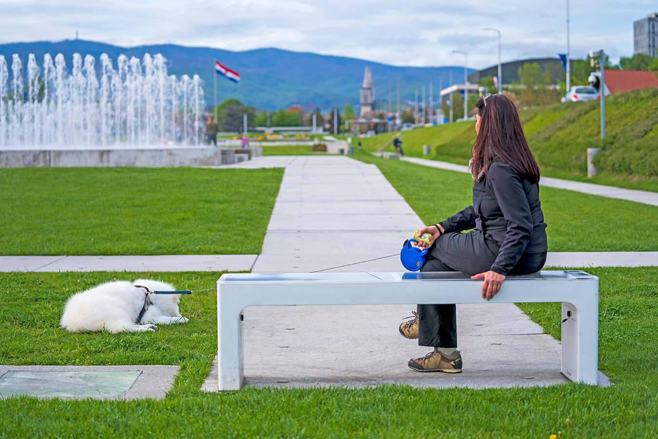 woman sitting on a solar bench